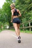 Running ung kvinna utomhus Arkivbild