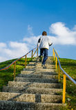 Running up the hill. Boy outdoor running up stairs to the top of a small hill Stock Images