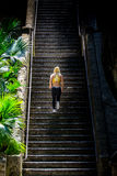 Running up the stairs. A young blonde woman runs up steps and stairs. She is beautiful, wearing a cheerleading sports dress , tiny pants, wears small earrings royalty free stock photography