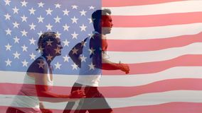 Running Video. Man and woman running outside with water bottles in the hands against american flag background stock footage