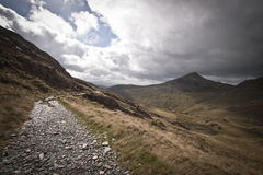 Running and walking path curving around the side of a Scottish mountain. Stone gravel path curving around the side of a mountain with the valley below.  A white Royalty Free Stock Images