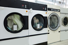 Running washing machines in laundry room Stock Images