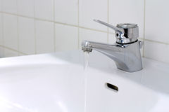 Running Water in the Bathroom. A water tap with clear water running down into the sink Royalty Free Stock Photo