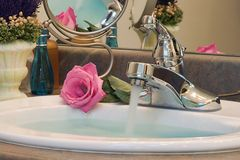 Running Water in Bathroom Sink. Bathroom sink with blue water running in basin and soft pink rose in background Royalty Free Stock Photo