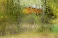 Running water drops. Closeup photo of rain drops running down glass window. House  and trees as background Royalty Free Stock Image
