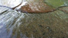 Running water on gray, brown asphalt. HD stock video