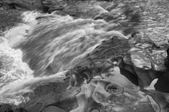 Running water over stone in black and white. stock images