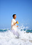 Running waves. Man running ocean waves with a lot of water drops stock photography