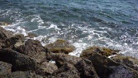 Running waves break on rocks on the beach stock video