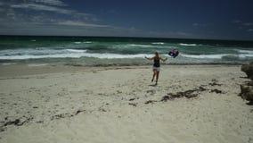 Running in Western Australia. Happy woman running on white beach waving Australian Flag. Blonde girl happiness jump in Mettams Pool, Trigg Beach, North Beach stock video footage