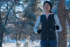 Running winter snow running girl runs through the Woods in winter sport winter. healthy lifestyle stock photos