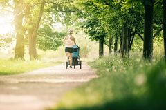 Running woman with baby stroller enjoying summer in park Royalty Free Stock Photos