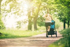 Running woman with baby stroller enjoying summer in park Royalty Free Stock Images