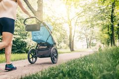 Running woman with baby stroller enjoying summer in park Stock Photography