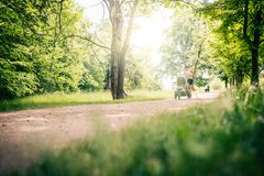 Running woman with baby stroller enjoying summer in park Stock Image