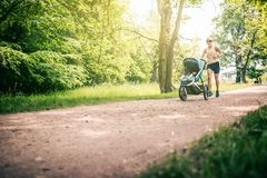Running woman with baby stroller enjoying summer in park Stock Photos