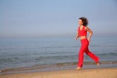 Running woman on beach Stock Photos