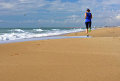 Running woman beach ocean. Copy space. Stock Image