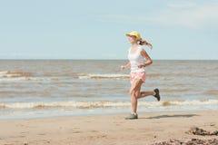 Running woman. Beautiful sports girl runs along the beach stock image