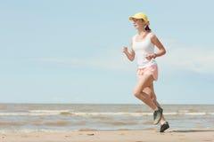 Running woman. Beautiful sports girl runs along the beach royalty free stock photo