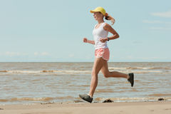Running woman. Beautiful sports girl runs along the beach royalty free stock photography