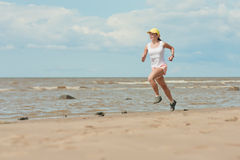 Running woman. Beautiful sports girl runs along the beach royalty free stock images