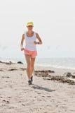 Running woman. Beautiful sports girl runs along the beach stock images
