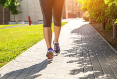 Running woman in black sports outfit (half body photo) on the sidewalk.  Stock Images