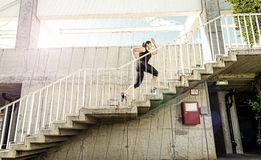 Running woman in black sports outfit, running up the stairs Royalty Free Stock Photo