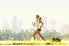 Running woman in city park - outdoor fitness. City fitness. Running in outdoor park. Woman runner outside jogging with Montreal skyline in background stock photo