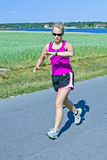 Running woman on country road Royalty Free Stock Photography