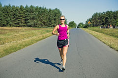 Running woman on country road Royalty Free Stock Image