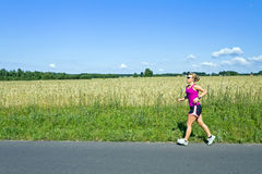Running woman on country road in summer Stock Images