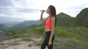 Running woman drink water on mountain road. Girl exercising outside in mountains