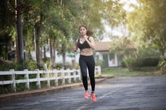 Running woman. Female runner jogging during outdoor  on road .Yo. Ung mixed race girl jogging Royalty Free Stock Photos