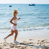 Running woman. Female runner jogging during outdoor workout on b Stock Photos