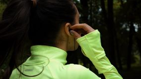 Running woman. Female runner jogging outdoor workout. Beautiful fit girl using her mobile phone headphones. stock video