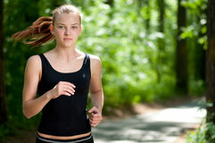 Running woman in forest Stock Images