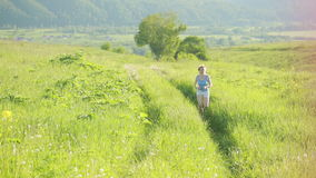 Running woman. Girl jogging on trail in mountains on field with grass in summer. Running woman. Girl jogging on trail in mountains on field with grass in summer stock footage