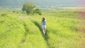 Running woman. Girl jogging on trail in mountains on field with grass in summer. stock video