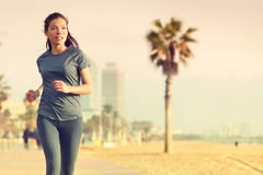 Running woman jogging on beach boardwalk. Healthy lifestyle girl runner training outside working out. Mixed race Asian Caucasian fitness woman exercising Royalty Free Stock Photo