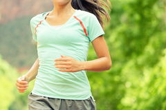 Running Woman Jogging On Sunny Day - Midsection. Running Woman Jogging. Midsection of determined woman runneron sunny day. Young female is in sports clothing Stock Photo