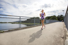 Running woman jogs in sunshine outdoor on bridge Stock Photos