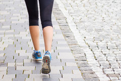 Running woman legs on cobbled road or street. Close up fitness background image with copy space Stock Image