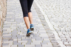 Running woman legs on cobbled road or street. Close up fitness background image with copy space Royalty Free Stock Photography