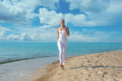 Running woman, outdoors portrait. Happy young woman in white clothes running on the beach Royalty Free Stock Image
