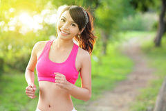 Running woman in park. Asian sport fitness model in sporty running clothes Royalty Free Stock Photo