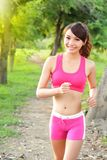 Running woman in park. Asian sport fitness model in sporty running clothes Stock Images
