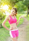 Running woman in park. Asian sport fitness model in sporty running clothes Stock Image