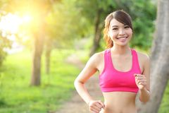Running woman in park. Asian sport fitness model in sporty running clothes Royalty Free Stock Photography
